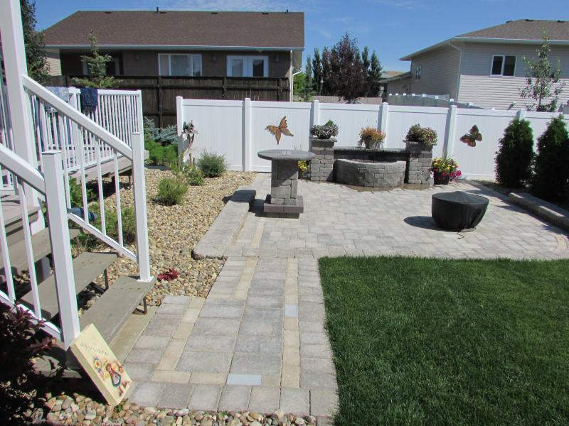 Swift Current backyard landscaped patio, outdoor fire pit, natural stone, outdoor accessories, rock