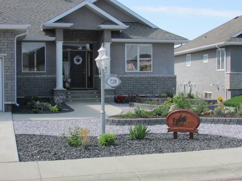 Swift Current residential landscaping, crushed rock, natural stones, flower beds, sidewalk, concrete